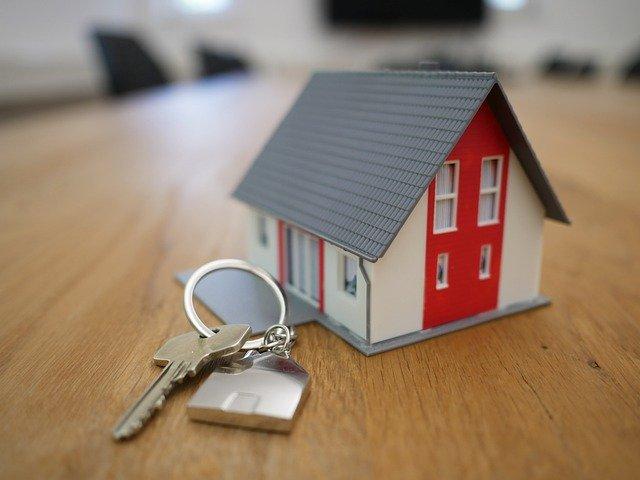 stůl a na něm malý domeček s klíčem