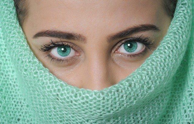 Žena s překrytým obličejem, jsou vidět pouze oči.